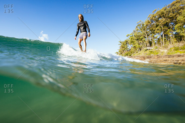 A man surfing with his toes on the nose of a longboard on a wave on a sunny day at Noosa National Park