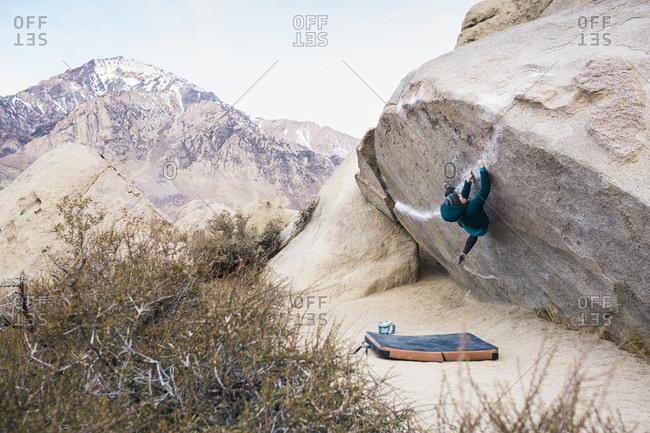 Woman rock climbing boulder above crash pad, Iron Man Traverse v4, Bishop, California, USA