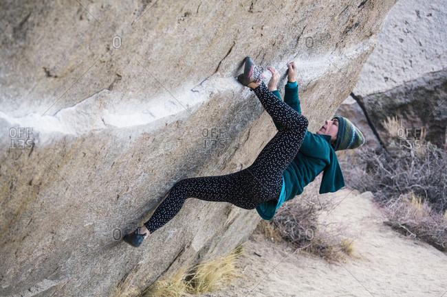 Side view of woman rock climbing boulder, Iron Man Traverse v4, Bishop, California, USA