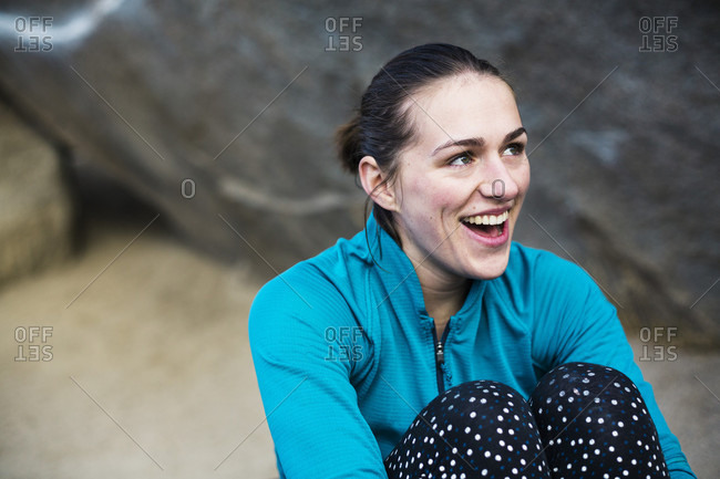 Smiling female rock climber sitting and looking away from camera