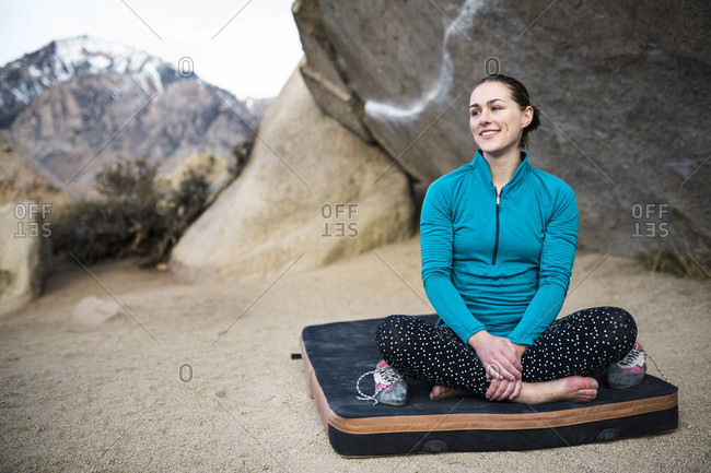 Smiling female rock climber sitting on crash pad and looking away from camera