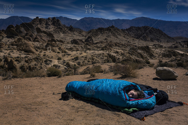 Woman sleeping in sleeping bag in desert at night, Alabama Hills, Lone Pine, California, USA