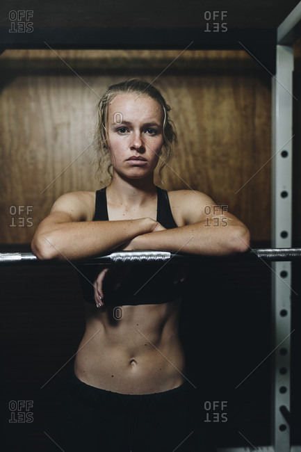 A young female athlete poses in a grungy home gym