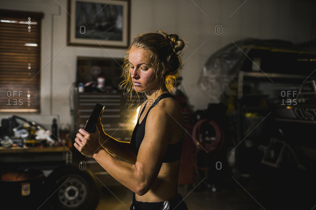 A young female athlete lifts weights in a smoky garage