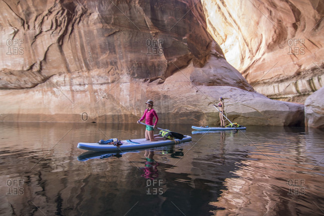 Two female athletes paddle through Cathedral in the Desert, a partially submerged sidearm of Glen Canyon, Utah, USA