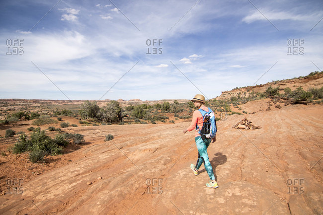 Rear view of lone woman backpacking through desert at Grand Staircase-Escalante National Monument, Utah, USA