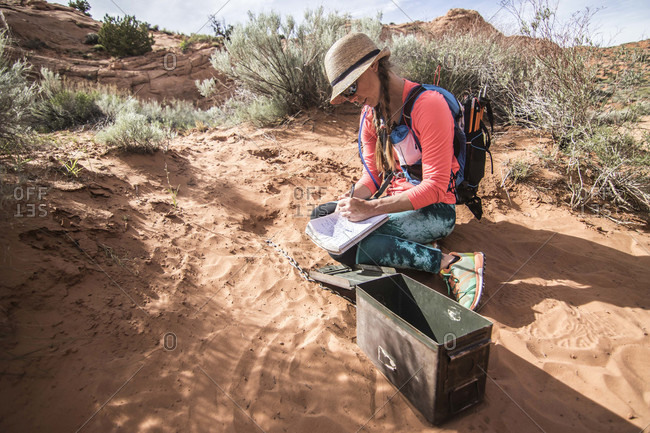 Female hiker crouching while entering her name into trail register while hiking through desert in Grand Staircase-Escalante National Monument, Utah, USA