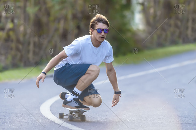 Young man in t-shirt, shorts and sunglasses skateboarding in street