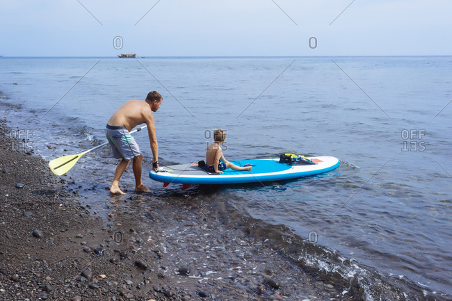Father and son at sup surfboard, Bali, Indonesia