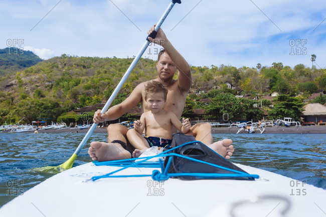 Father and son on sup surfboard, Bali, Indonesia