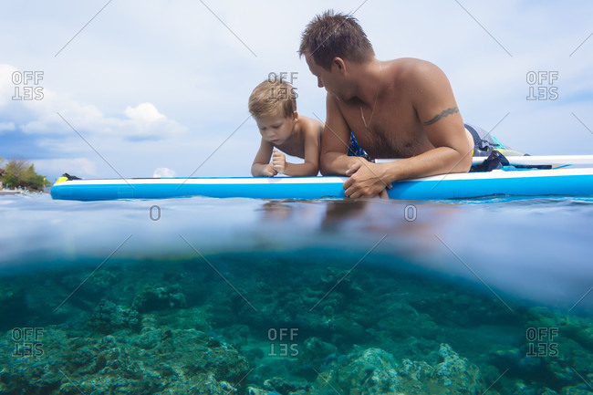 Father and son with surf board in ocean, Bali, Indonesia