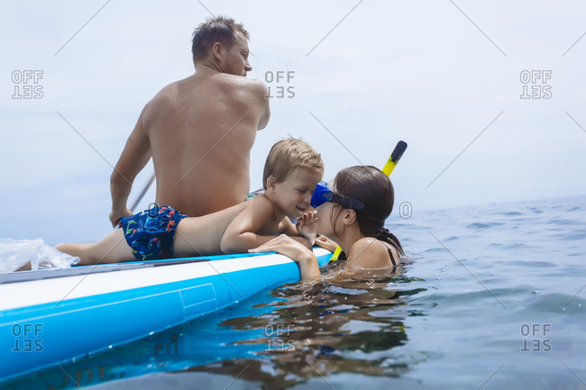 Family on sup surfboard in ocean, Bali, Indonesia