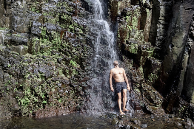 Full length of man standing under waterfall, La Gomera, Canary Islands, Spain