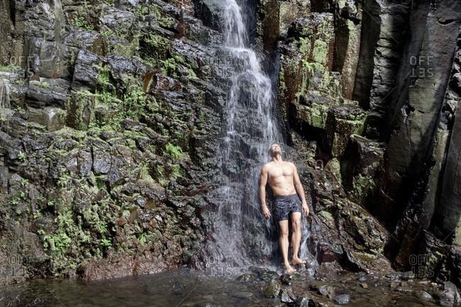 Full length of man standing under waterfall, La Gomera, Canary Islands, Spain
