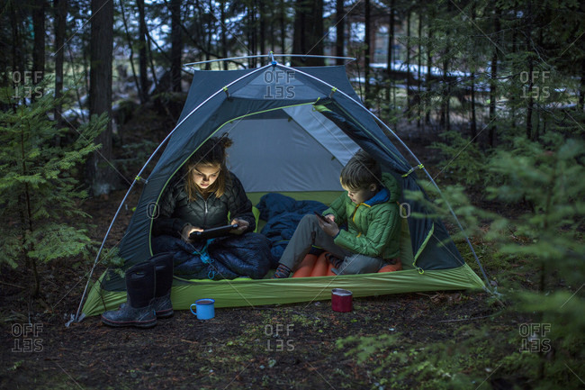 Boy and girl using tablet and smartphone while camping together inside tent pitched in forest, Sandpoint, Idaho, USA