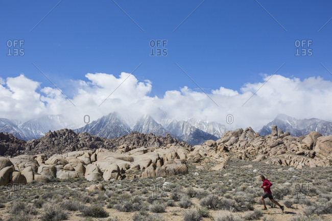 Adult man jogging across bushy desert in front of heaps of boulders and mountain range in background, Lone Pine, California, USA