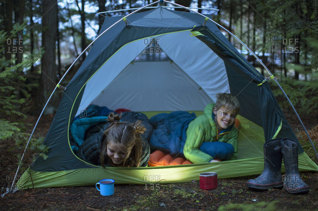 Boy and girl laughing while lying in sleeping bags inside tent pitched in forest, Sandpoint, Idaho, USA