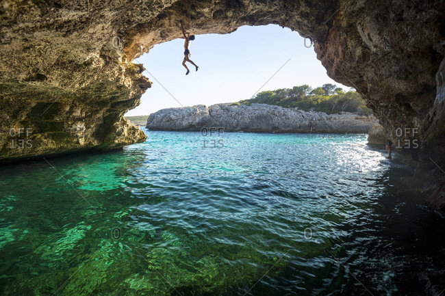 Adventurous rock climber climbing challenging route across natural arch, Cala Varques, Manacor, Mallorca, Spain
