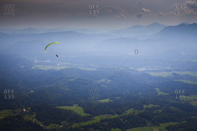 Distant view of a paraglider flying high above the mountain valley of Begunje and Radovljica, after taking off from Dobrca mountain, Upper Carniola, Slovenia