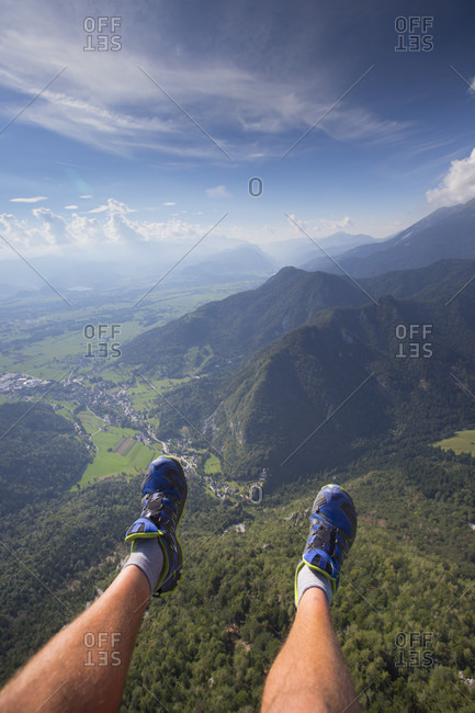 The feet of a paraglider are dangling high above the Slovenian Alps during a paragliding flight from the Dobrca mountain near Begunje and Radovljica in Slovenia