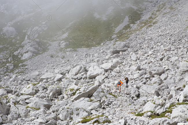 Two hikers are walking in rocky terrain of Mount Krn in southwestern Julian Alps, Slovenia