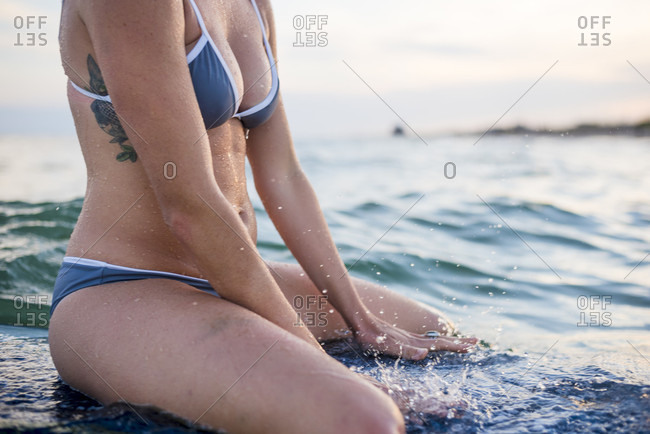 Mid section shot of young woman in bikini sitting on surfboard in sea