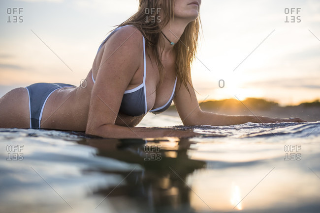 Side view of young woman in bikini paddling on surfboard in sea at sunset