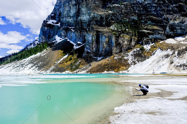 Person on shore of Lake Louise in winter, Banff National Park, Canada