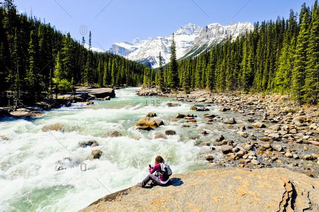 Woman sitting on riverbank at Mistaya Canyon, Banff National Park, Canada