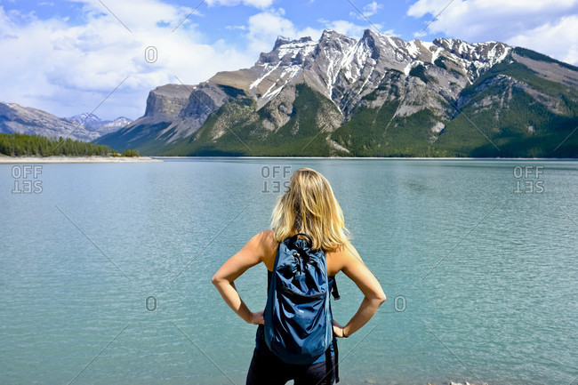 Rear view of female backpacker on shore of Lake Minnewaka, Banff National Park, Canada