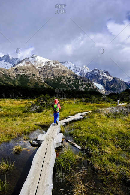 Rear view of backpacker hiking along trail in scenery with mountains, El Chalten, Santa Cruz Province, Patagonia, Argentina