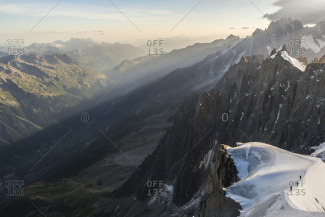 View from Aiguille du Midi peak of sunlight illuminating valley in French Alps, Haute-Savoie, France