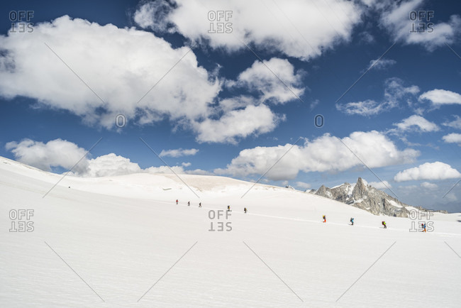 Clouds over group of hikers crossing snowcapped glacier in French Alps, Haute-Savoie, France