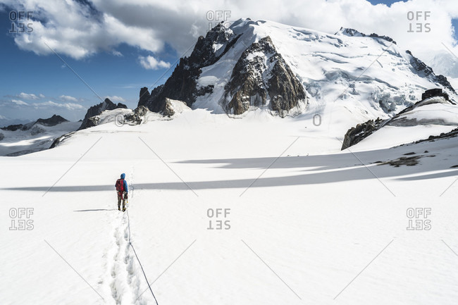 Mountaineer crossing snowcapped terrain in front of Mont Blanc du Tacul, Haute-Savoie, France