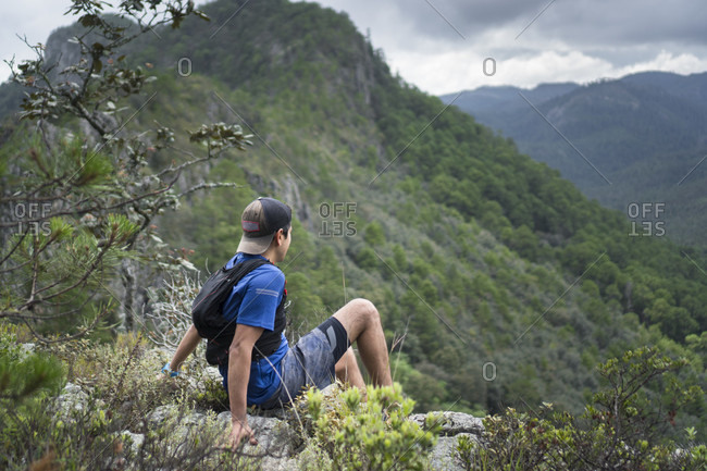 Young man sitting and looking at view of mountains, Hidalgo, Mexico