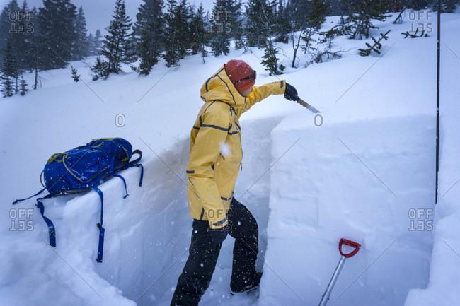 Person creating pit by cutting heap of snow to study snow layers, Aspen, Colorado, USA