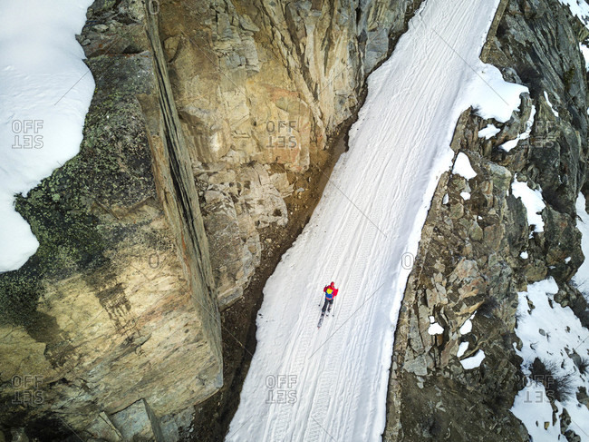 Aerial view of skier ascending snowcapped path beside rock wall, Aspen, Colorado, USA