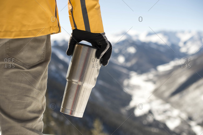 Arm of man holding thermos while standing outdoors against mountain valley, Aspen, Colorado, USA