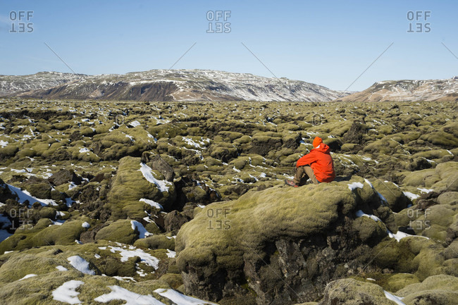 Male hiker sitting alone on mossy lava field and contemplating, Iceland