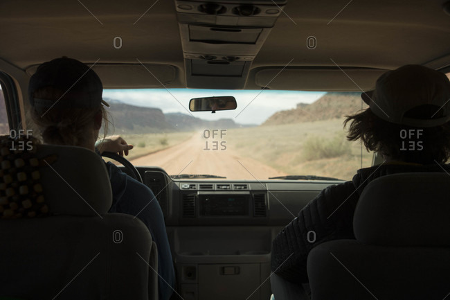 Vehicle interior view of two people following up dirt road on way to rock climbing spot, Moab, Utah, USA