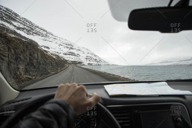 Adventurer drives along fjord in Westfjords of Iceland