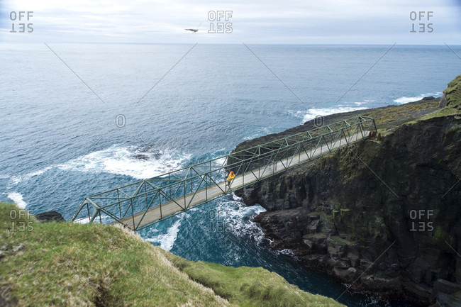 Adventurer stopping on bridge between two of Faroe Islands to enjoy view