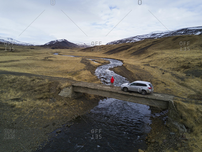 Adventure looking into Westfjords landscape from bridge with SUV in Iceland