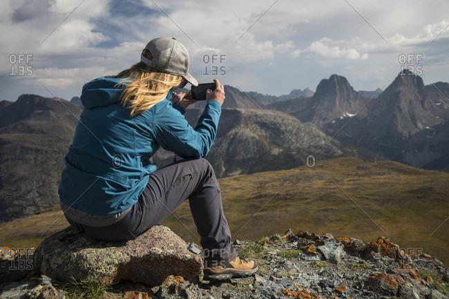 Woman photographing view of San Juan mountains, Silverton, Colorado, USA