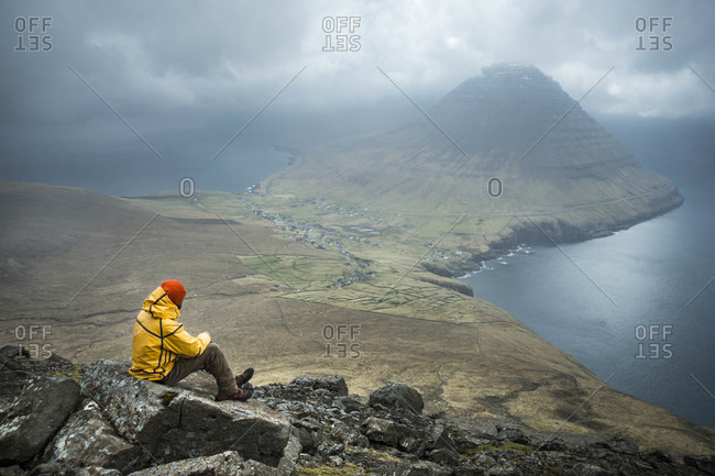 Hiker looking at view of coastline and mountain, Faroe Islands