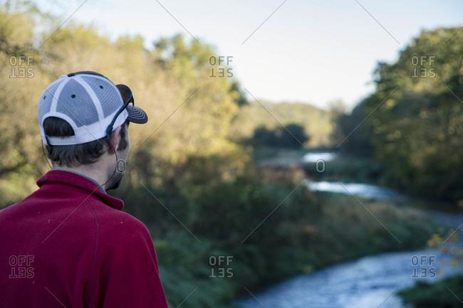 Rear view of man looking at winding river, Galena, Illinois, USA