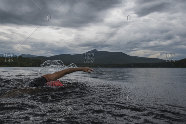 Swimmer in Lake Chocorua with Mount Chocorua in background, New Hampshire, USA
