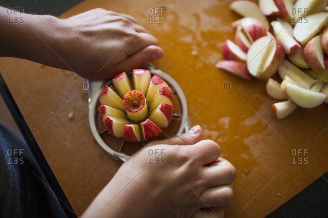 Hands of person slicing apple with apple slicer for apple sauce
