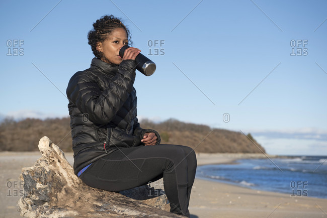 Woman with black curly hair drinking coffee from thermos at beach