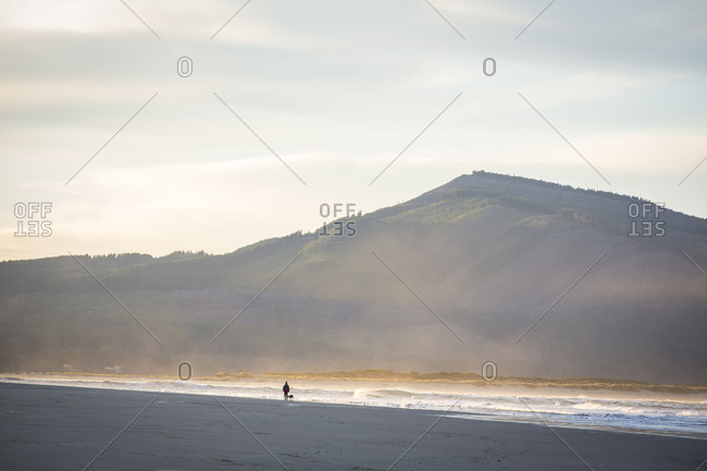 Woman in the distance walking the dog at sunrise on beach of Netarts Bay, Oregon, USA